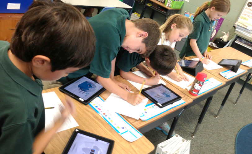 Young pupils using the Samsung School App in classroom