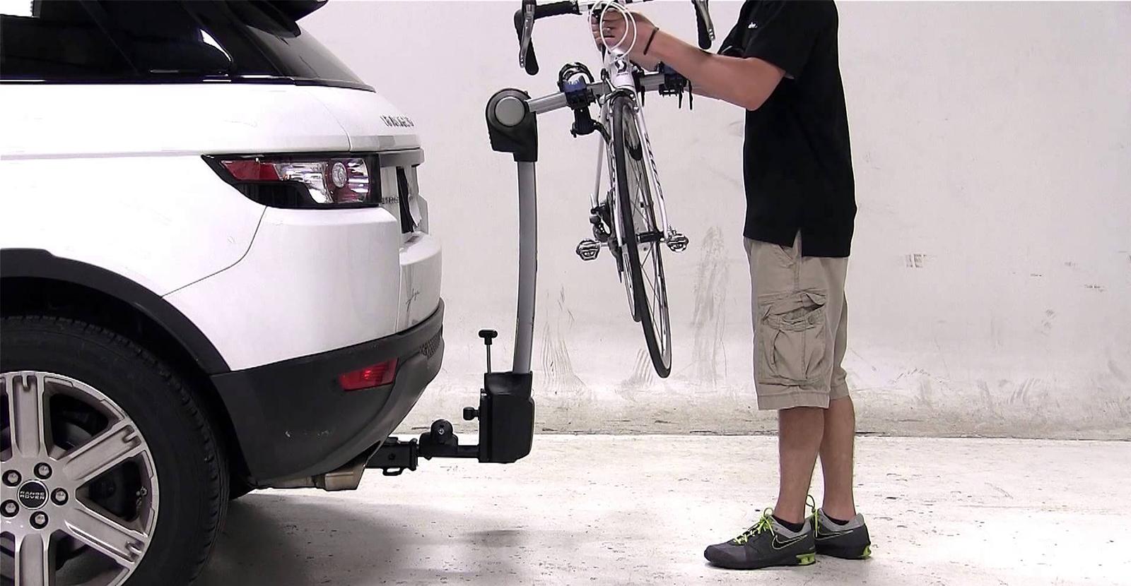 Man putting bike on a car mounted bike rack